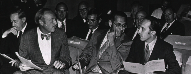 A group of men sit talking in a reserved section at the front of an auditorium holding programs.