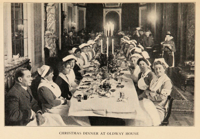 Christmas Dinner at Oldway House, many uniformed women sit a a very long candlelit dining table in a marble columned room.