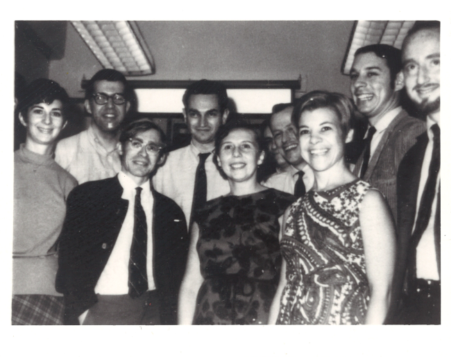 A group of people pose in a hallway.