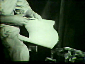 A figure uses scissors on paper to cut out a bandage.