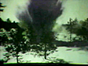 A Finnish winter landscape with snow and trees. An explosion sending debris in the air fills the center of the picture.