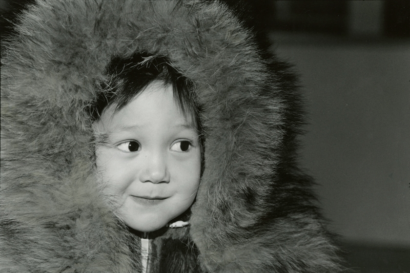 A smiling young boy in a winter hood.