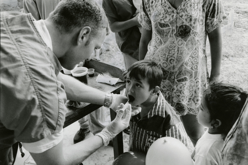 Volunteer Medical School student Clinton Keilman administers oral medication to children.