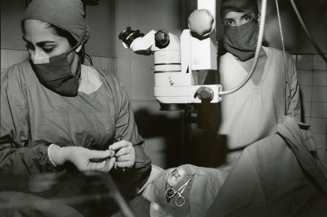 Women in surgical masks work in a room with optical equipment.