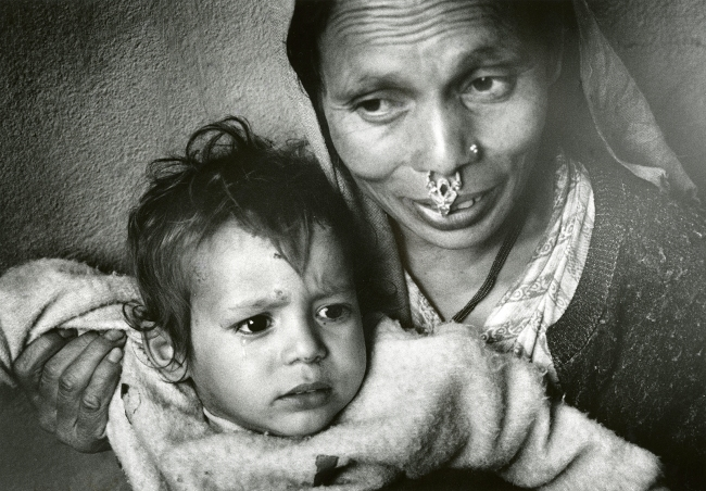 A woman holds a young child.
