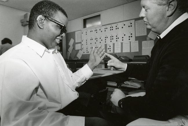 Two men converse.