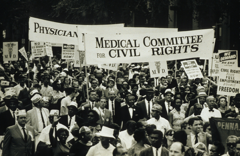 A group of people, black and white, men and women, in suits and dresses march under a banner reading Medical Committee for Civil Rights.
