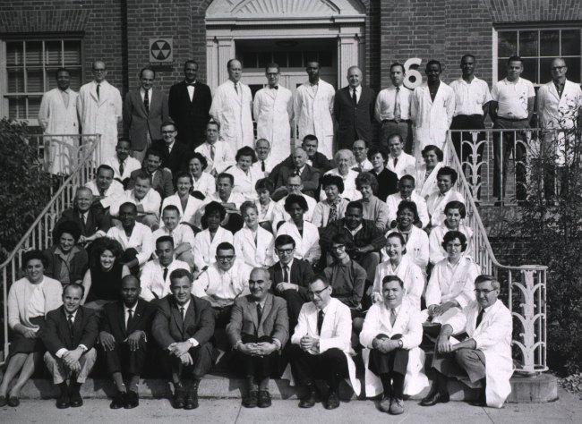A large, diverse group of people, many in lab coats, fit on the steps of a large building.