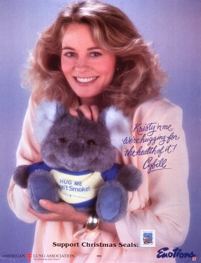 "Cybill Shepherd holds a toy koala bear wearing a t-shirt that reads ""Hug me, don't smoke."""
