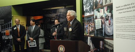 Lindberg speaks at a podium in front of the entrance to the Against the Odds exhibition at the National Library of Medicine.