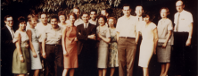 A group of about 20 people pose for a photograph outside.
