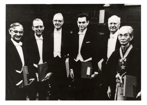 Six men in formal dress stand together for a photograph.