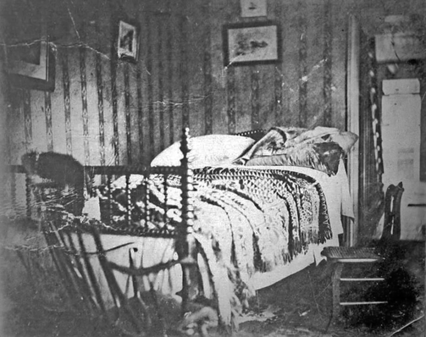 A photograph of a bed in a wallpapered room.