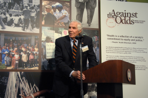 Lindberg stands at a podium in front of the title panel for the Against the Odds Exhibtion