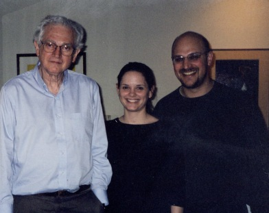 Three people pose together in a home.