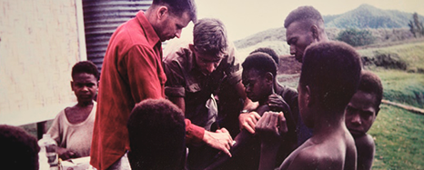 Two white men take blood from a young black youth outside a building, other black adults and youths look on.