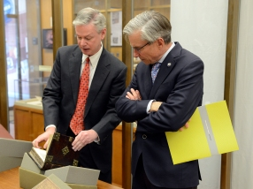 The Chairman looks at a leather bound book handled by Michael North.