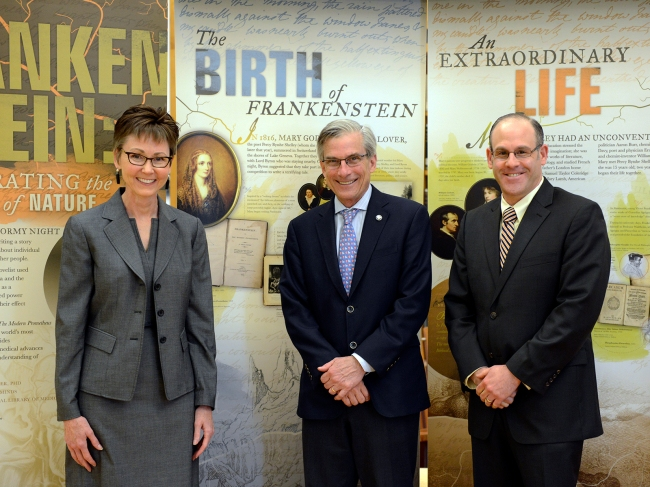 Staff pose with the Chariman of NEH in front of the Frankenstein Exhibition banners.