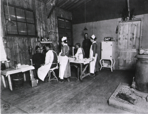 In a wooden building with a wood stove, female nurses stand behind men in white aprons seated accross from patients.