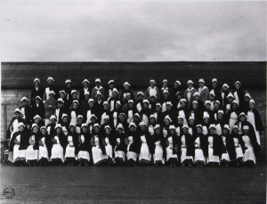 Eighty two people, posed outdoors in 5 rows. Nurses in uniform, white caps and aprons and dark capes.
