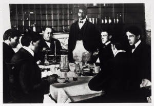 A group of men sit around a dining table, one weighs cake on a balance scale.