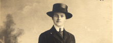 A photograph of a woman in a dark jacket and tie and a hat.