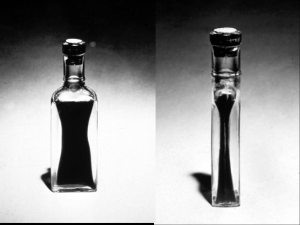 Photogaphs of clear bottles filled with dark liquid, showing the thickness of the glass sides.