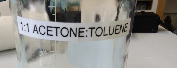 A bottle of clear liquid labeled 1:1 Acetone:Toluene.