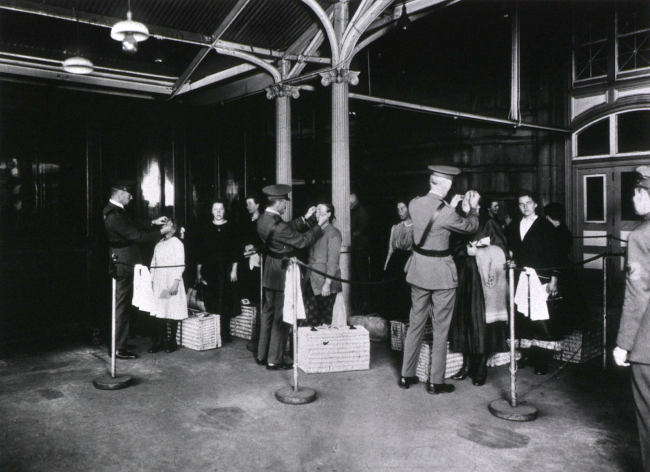 Uniformed men inspect the eyes of people, with luggage, waiting in lines.