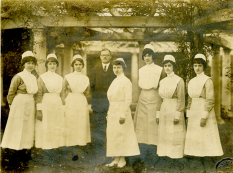 A group of seven women in nursing uniforms stand with a man in a suit under an arbor.