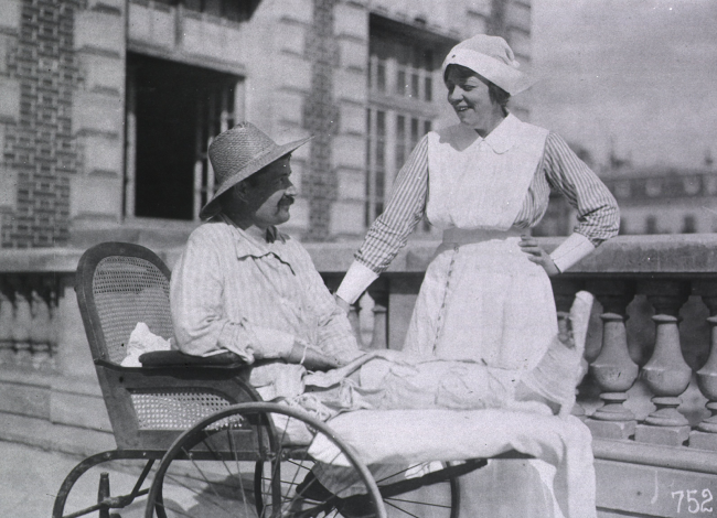 A nurse smiles down at a man in a wheelchair with a bandaged leg and a straw hat.