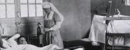 Nurses wait on patients in hospital beds.