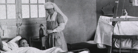 Nurses wait on patients in hospital beds.