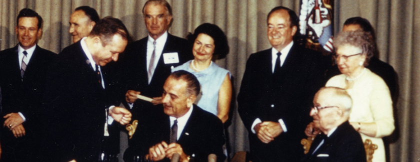 President Johnson seated at a table with a rack of pens, surrounded by onlookers.