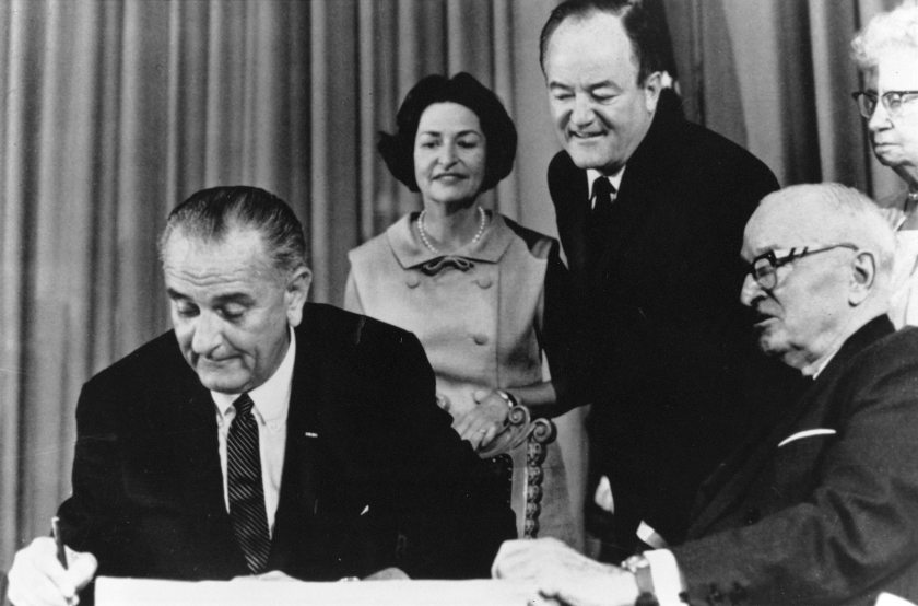 President Johnson signs while four othrs look on.