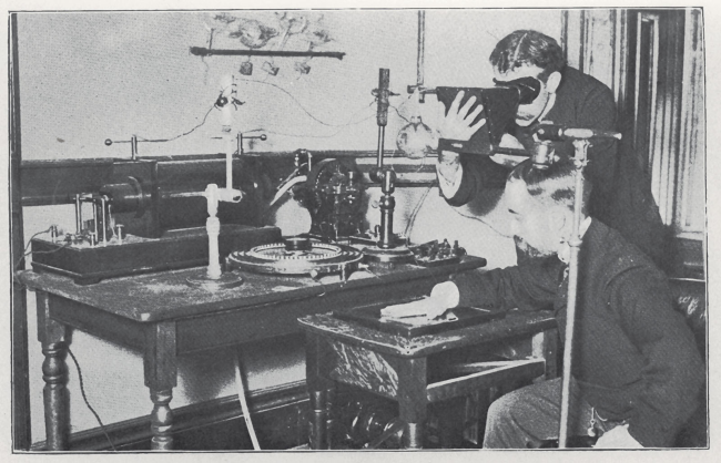 A man looks through a viewer while another man holds his hand flat on a glass plate, they are surrounded by complex equipment on wooden tables.