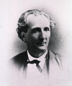 A formal vignette portrait of a man with a ribbon tie.