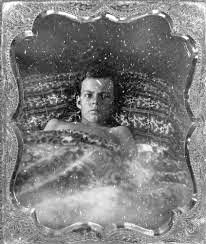 A scratched and grainy image of a young man in a bed in an ornate frame.