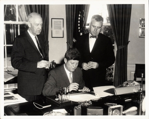 John E. Fogarty and Senator Lister Hill watch President John F. Kennedy sign the 1962 appropriations bill at a desk in the White House.