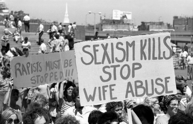 "Crowd of people marching holding anti-domestic violence signs that read ""Rapists must be stopped!!!"" and ""Sexism Kills Stop Wife Abuse""."