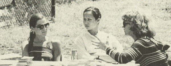 Three women sitting at a table, one leans forward gesturing..