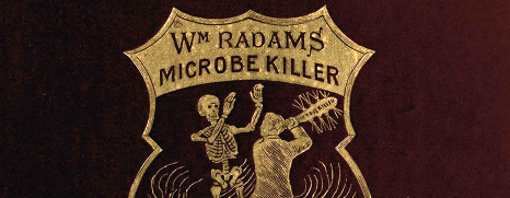 An embossed gold shield featureing a man threatening a skeleton with a weapon labeled Microbe Killer.