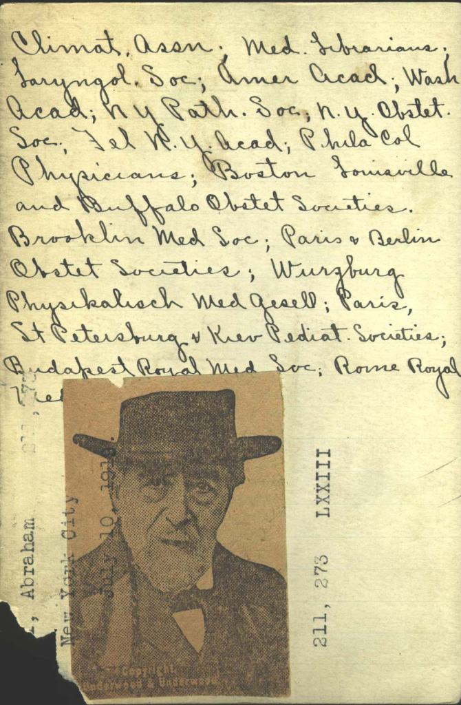 A handwritten card with a small newspaper photograph glued on it.