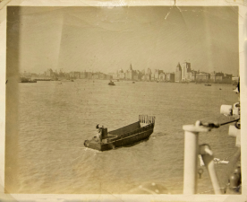 The Shanghai skyline with a small transport boat in the foreground