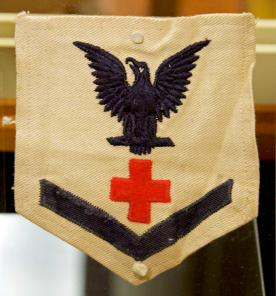 A square white cloth patch, pointed at the bottom, with a blue chevron, a red cross and a blue eagle.