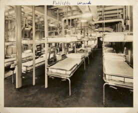 A room of cots with hanging cots above each.