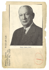 A halftone newspaper photo of a man in a suit pasted to an index card.