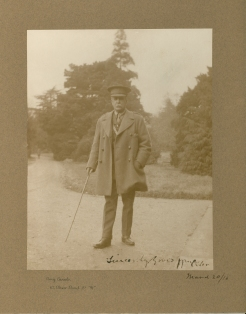 A photograph of a man in a uniform and coat with a walking stick standing on a country street.