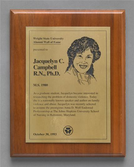 A wooden plaque with engraved brass text and portrait of Jaqueline Campbell