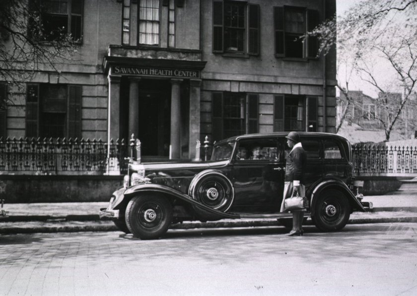 Exterior view of the Savannah Health Center. An African American woman is standing by an automobile.